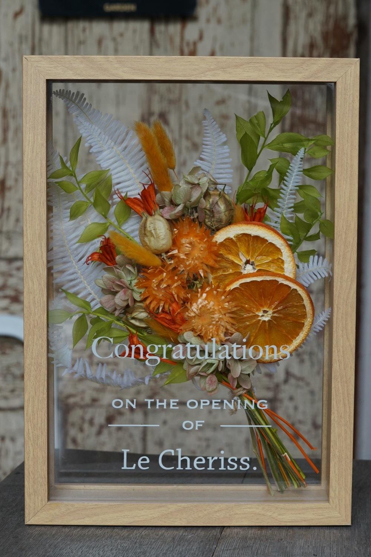 「ずっと夢だったお店をオープンさせた友達へ」オレンジ色がメインのドライフラワーの開店お祝いのフレームアレンジ