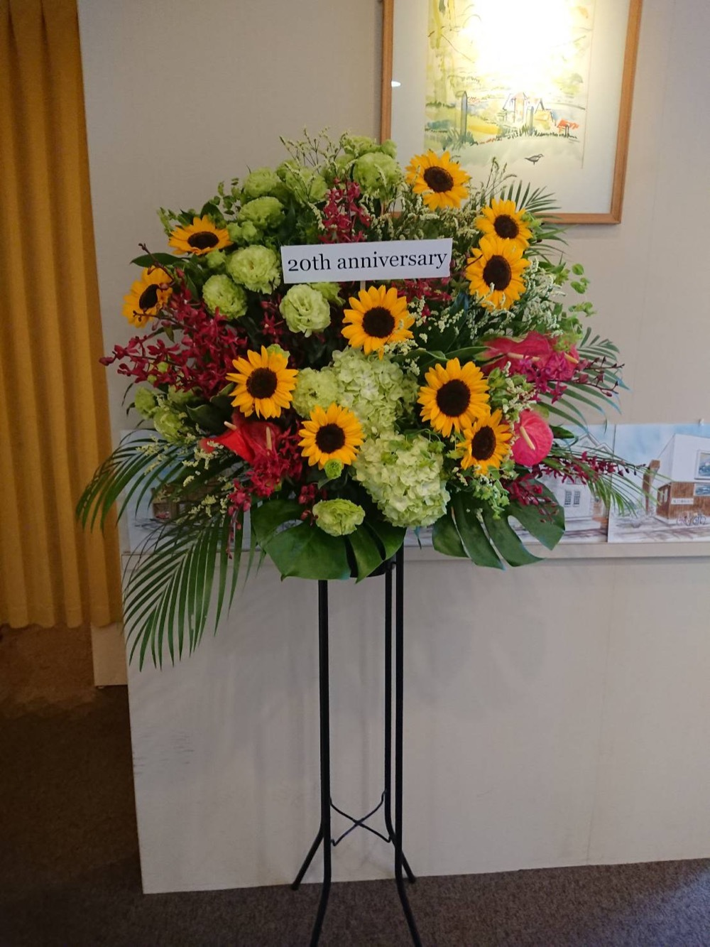 会社のロゴマーク色でおつくりした20周年お祝いのスタンド花