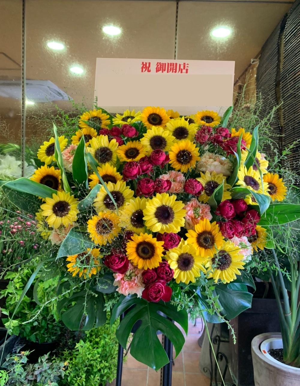 カフェオープンをお祝いする黄色をメインとした華やかな雰囲気のスタンド花