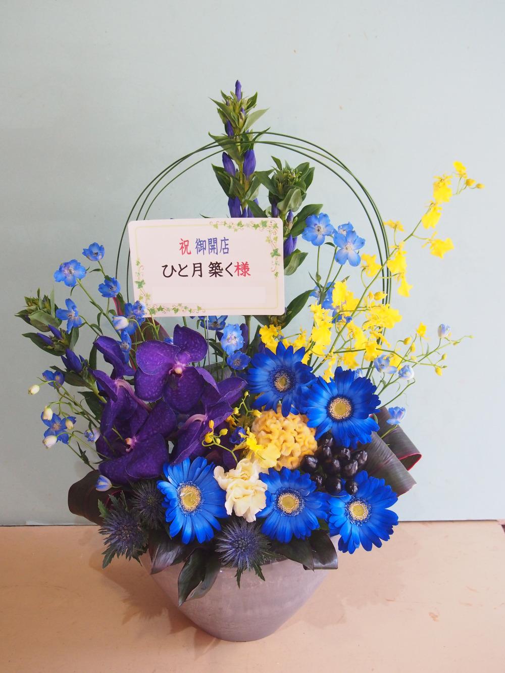 お店のイメージにあわせておつくりしたブルーと黄色の開店お祝い花