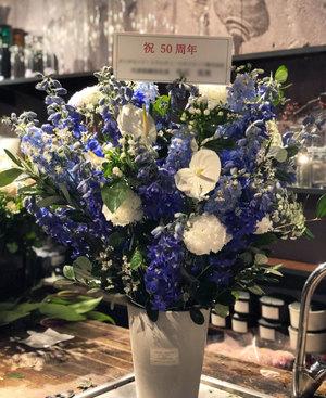 コーポレートカラーにアンスリウムを添えた爽やかな周年祝い花