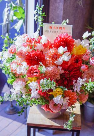銀行さまの60周年を祝う 華やかなピンクオレンジの周年祝い花
