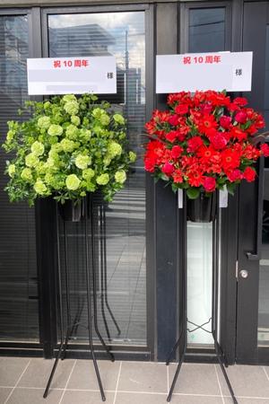 2つのグループのメンバーカラーの赤と緑のスタンド花
