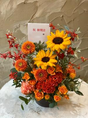 お店のロゴのオレンジ色をベースにしたレストラン開業お祝い花