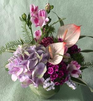 紫の花々が優しく上品なお祝いアレンジメント